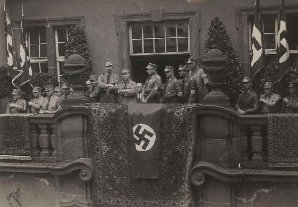 Nach der Amtseinführung von Oberbürgermeister Otto Wittgen am 16.3.1933 auf dem Balkon des Rathauses. Von links nach rechts (über dem Teppich): Kreisleiter Albert Müller, Gauleiter Gustav Simon, Wittgen (über der Hakenkreuzfahne), die Kommissare Ludwig Christ und Oskar Peter Hildebrandt